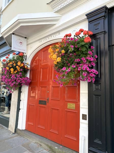 Orange door with flowers on the sides