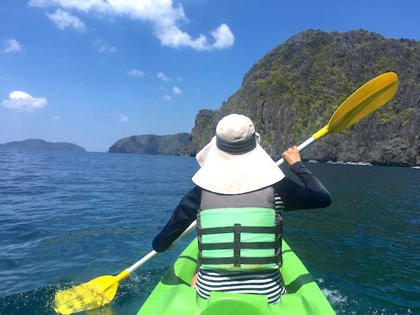 kayaking with a rash guard and cotton hat