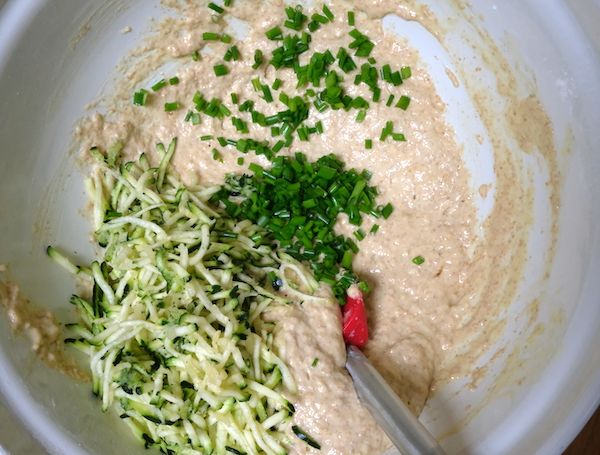 Adding courgette and chives to the batter