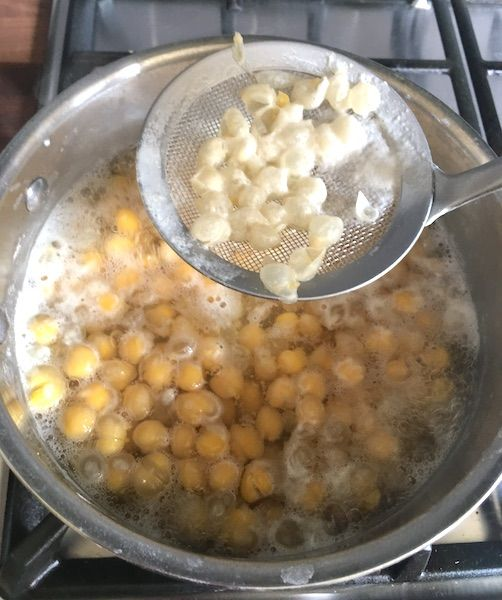 Removing floating skin of chickpeas with a sieve spoon