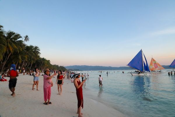 Busy White beach at sunset