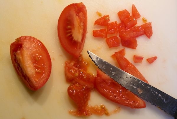cutting tomatoes on a chopping board