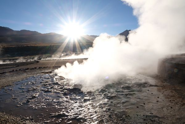 Water and steam - geyser and sun coming  behind the mountains
