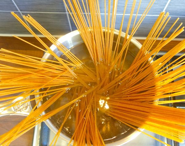 Whole wheat spaghetti going in the pot with salted water