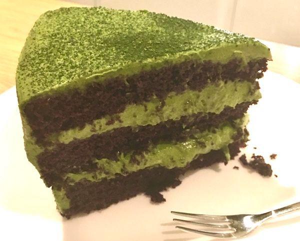 A slice of Dark Chocolate & Matcha Cream Cake with the cream soft...