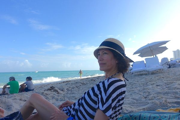 at the beach with a straw hat