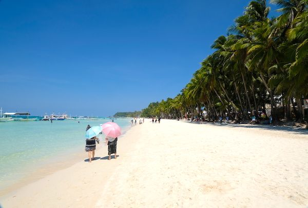 Tourists walking on the beach and protecting themselves from the sun - White beach Station 2